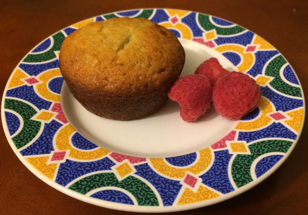 vegan banana bread muffin on plate with raspberries