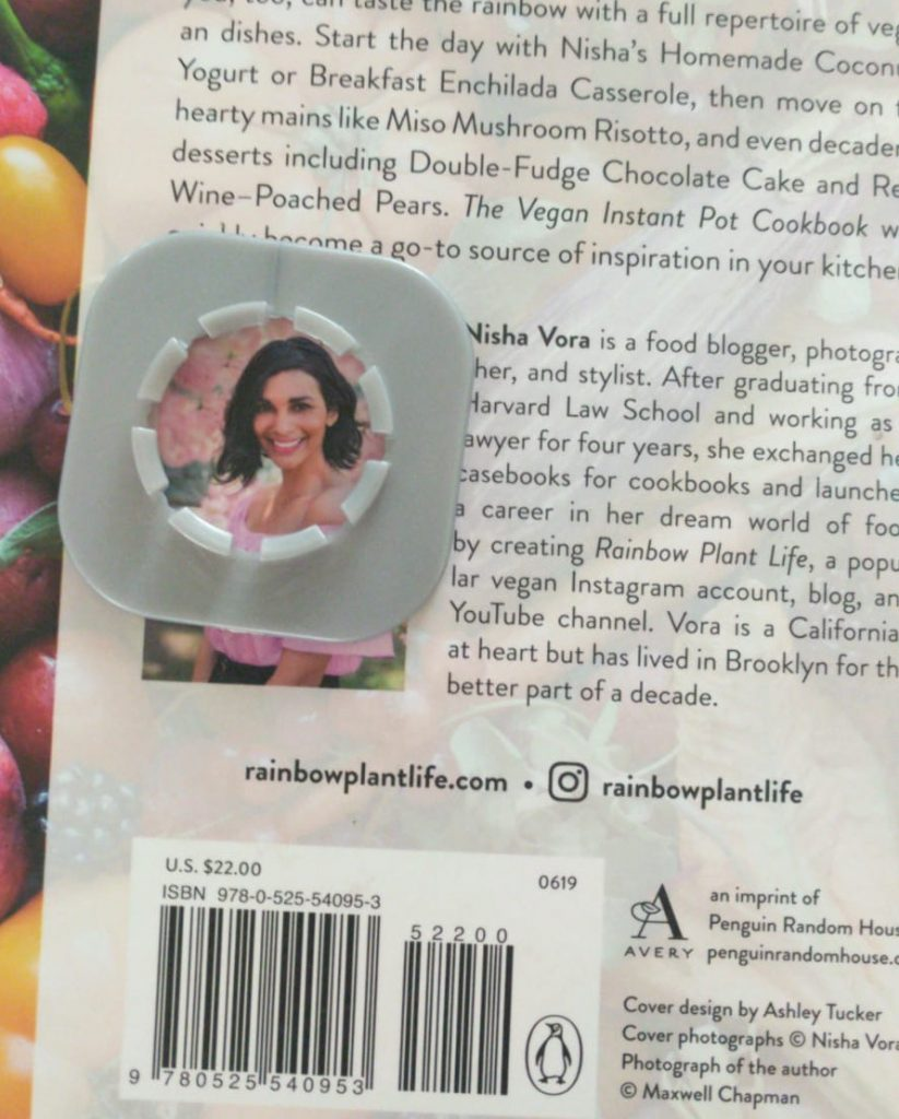 Nisha Vora's back cover photo on The Vegan Instant Pot framed by a toy