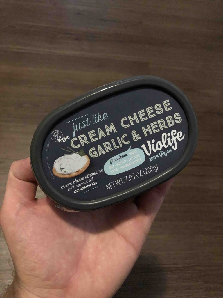 hand holding tub of cream cheese