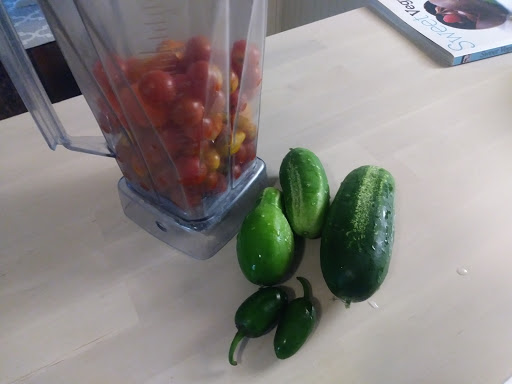 cherry tomatoes in a blender with cucumbers and jalapeños next to it